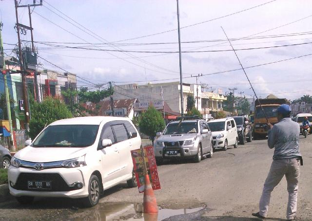 Warga Sambil Mengeluh, Mancing Ditengah Jalan Lintas Pasir Pengaraian-Ujungbatu