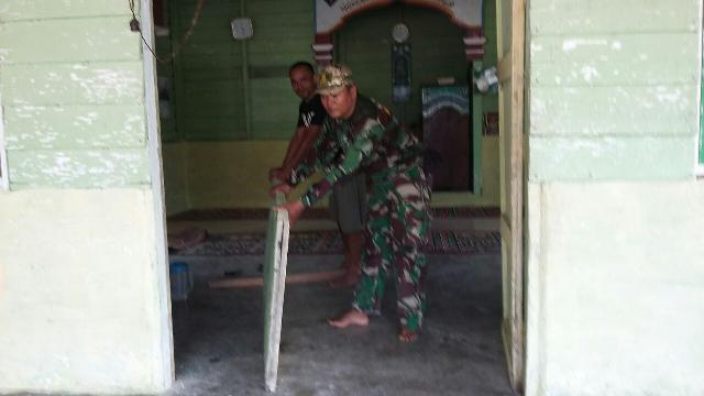 Sertu Herius Bantu Warga Perbaiki Pintu Musollah Darus Salam Yang Rusak